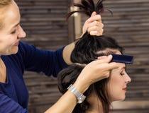 Elegante vrouw in schoonheidszaal De kapper doet kapsel in de vorm van grote krul Het kapsel van het conceptenhuwelijk royalty-vrije stock afbeeldingen