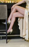 Elegante vrouwenbenen die in een luxestaaf zitten Royalty-vrije Stock Afbeeldingen