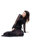 Elegante vrouwenzitting op een vloer en neer het kijken stock afbeelding