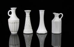 4 elegante weiße Vasen auf schwarzem Hintergrund Stockfotos