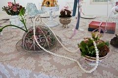 Elegante Weinleseperlen und -blumen auf einer Seidenspitzetischdecke stockfotografie