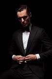 Elegante zakenman in het zwarte kostuum stellen gezet in donkere studio Stock Fotografie