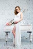 Elegante zwangere vrouw in een klassieke witte kleding dichtbij de witte piano Royalty-vrije Stock Foto's