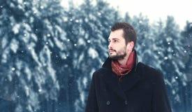 Eleganter bärtiger brunette Mann der Mode geht in Winter, schaut weg lizenzfreie stockfotos