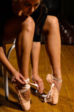 Eleganter Balletttänzer, der ihre pointe Schuhe bindet Lizenzfreies Stockfoto