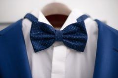 Eleganter blauer Anzug der Nahaufnahme mit weißem Hemd und blauer Fliege, in Vorbereitung auf ein formales Ereignis stockfotografie