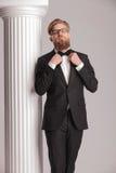 Eleganter blonder Mann, der sein bowtie repariert Stockbilder