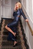 Eleganter blonder trinkender Wein im Abendkleid auf der Treppe Lizenzfreie Stockfotografie