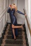 Eleganter blonder trinkender Wein im Abendkleid auf der Treppe Stockbild