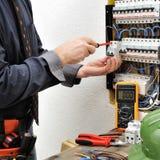 Eleganter Elektrikertechniker bei der Arbeit über ein Wohnelektrisches Stockbild