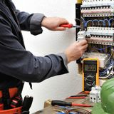 Eleganter Elektrikertechniker bei der Arbeit über ein Wohnelektrisches Lizenzfreie Stockfotografie