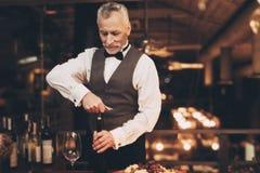 Eleganter erfahrener Sommelier, der Flasche Wein im Restaurant entkorkt Ein Becher Wein in der Hand stockfotografie