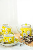 Eleganter gelber Teesatz mit Blumenverzierung auf gealterter hölzerner Tabelle, Blumenstrauß von Weiden, Frühling, Ostern-Brunch  Lizenzfreies Stockfoto