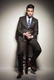 Eleganter Geschäftsmann, der auf einem Schemel, denkend sitzt Stockfoto