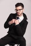 Eleganter Geschäftsmann, der auf einem Schemel sitzt Stockfoto