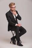 Eleganter Geschäftsmann, der auf einem Schemel sitzt Lizenzfreie Stockfotografie