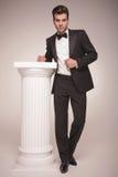 Eleganter Geschäftsmann, der auf einer weißen Spalte sich lehnt Lizenzfreie Stockbilder