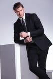 Eleganter Geschäftsmann, der auf einer weißen Würfeltabelle sich lehnt Stockfoto
