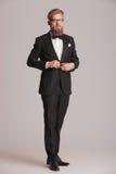 Eleganter Geschäftsmann, der auf grauem Studio backgroud steht Lizenzfreies Stockfoto