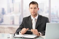 Eleganter Geschäftsmann, der im hellen Büro sitzt Stockbilder