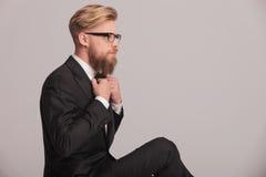 Eleganter Geschäftsmann, der sein bowtie repariert Stockfotos