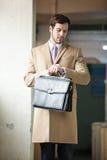 Eleganter Geschäftsmann, der seine Uhr betrachtet lizenzfreies stockbild