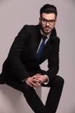 Eleganter Geschäftsmann, der zusammen mit seinen Händen sitzt Stockbild
