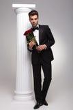 Eleganter Geschäftsmann, der einen Blumenstrauß von roten Rosen hält Stockfotografie