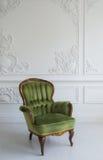 Eleganter grüner Lehnsessel im sauberen hellen weißen Luxusinnenraum Lizenzfreies Stockfoto