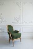 Eleganter grüner Lehnsessel im sauberen hellen weißen Luxusinnenraum Stockfotos