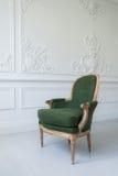Eleganter grüner Lehnsessel im sauberen hellen weißen Luxusinnenraum Lizenzfreie Stockfotos