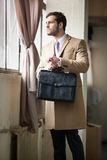Eleganter junger Geschäftsmann, der heraus das Fenster schaut. lizenzfreie stockbilder