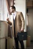Eleganter junger Geschäftsmann, der heraus das Fenster schaut. lizenzfreie stockfotografie