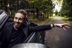 Eleganter junger glücklicher Mann im konvertierbaren Auto im Freien. Stockbild