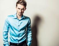 Eleganter junger gutaussehender Mann im blauen Seidenhemd Mann entfernen irgendjemandes Kleidung Stockfoto
