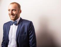 Eleganter junger gutaussehender Mann im dunkelblauen Kostüm u. in der Fliege Mann entfernen irgendjemandes Kleidung Lizenzfreie Stockfotos