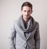 Eleganter junger gutaussehender Mann im grauen Kostüm Mann entfernen irgendjemandes Kleidung lizenzfreie stockfotos