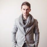 Eleganter junger gutaussehender Mann im grauen Kostüm Mann entfernen irgendjemandes Kleidung Lizenzfreie Stockbilder
