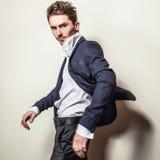 Eleganter junger gutaussehender Mann im Kostüm Mann entfernen irgendjemandes Kleidung Stockfoto