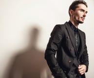 Eleganter junger gutaussehender Mann im schwarzen Kostüm Mann entfernen irgendjemandes Kleidung Lizenzfreies Stockfoto