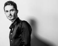 Eleganter junger gutaussehender Mann im schwarzen Seidenhemd Schwarz-weißes Porträt der Studiomode Stockfoto