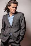 Eleganter junger hübscher langhaariger Mann im Kostüm. stockfotografie