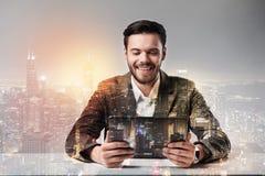 Eleganter junger Mann, der den Schirm einer Tablette betrachtet lizenzfreie stockfotos