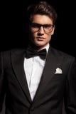 Eleganter junger Mann, der ein Smoking und Gläser trägt Stockbilder