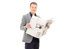 Eleganter junger Mann, der eine Zeitung liest Stockbild