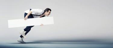 Eleganter Mann, der mit einem weißen Brett läuft Lizenzfreies Stockbild