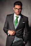 Eleganter junger Mann in der Smokingsjacke, die Knopf hält Lizenzfreie Stockfotos