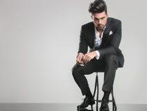 Eleganter junger Mann im Smoking, das auf einem Schemel sitzt Lizenzfreie Stockbilder