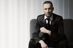Eleganter junger Modemann im Smoking auf einem Sofa, Vorhanghintergrund Lizenzfreie Stockfotos