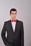 Eleganter junger Modemann im Smoking hält seine rechte Hand herein Stockbilder